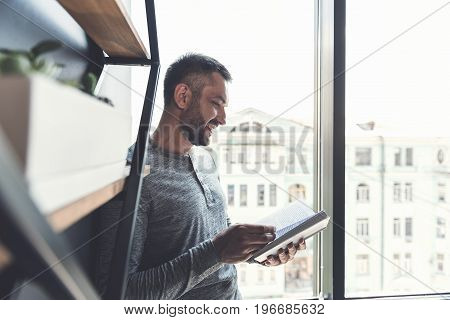 Favorite book. Cheerful adult businessman is standing on window background with opened novel and expressing gladness. Selective focus and copy space in the right side