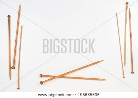 Wooden knitting needles frame on white background with copy space for text