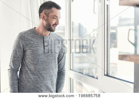 Sense of curiosity. Positive stylish adult businessman with stubble is looking through window inquisitively while standing in modern office. Copy space in the right side