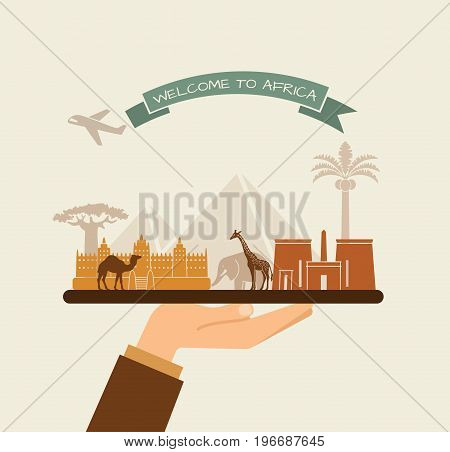 The hand holds the sights of Africa on a tray. The plane and the words welcome to Africa on the ribbon
