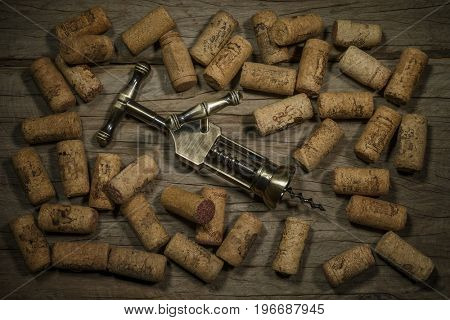 Corkscrew and wine corks as background, selective focus close up, top view