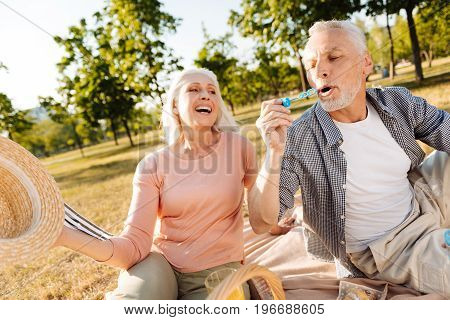 Want to catch them. Infatuated male person keeping mouth opened while blowing bubbles and holding arm with stick in front of lips