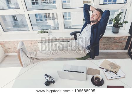 Feeling comfortable. Top view of satisfied bristled man is relaxing in chair while holding his hands behind head and putting legs up on his table. Window with cityscape on background