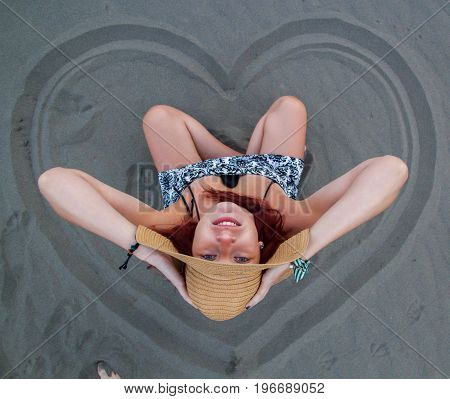 A Redhead Girl With A Hat On Her Head Sits In The Sand On The Beach, A Drawn Heart In The Sand Aroun