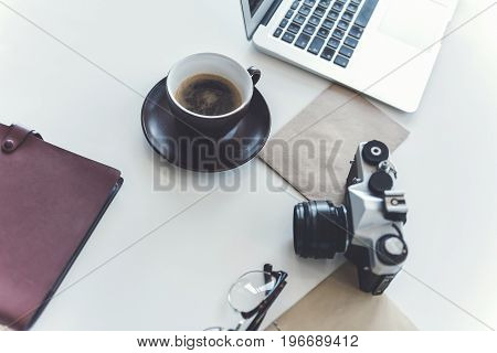 Coffee break. Close-up top view of workplace with cup of hot espresso, camera and other things