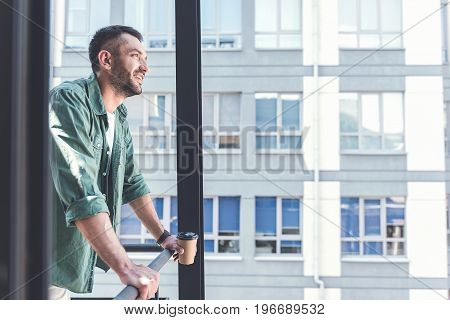 Feeling great. Satisfied attractive man is leaning on railing and enjoying view while drinking espresso. Copy space in the right side