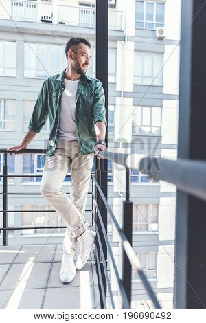 Confident look. Lovable bristled male in casual wear leaning at handrails and expressing gladness while standing on cityscape background