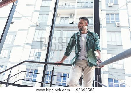 Feeling great. Low angle of attractive adult man with stubble is leaning on railing and looking aside with smile. Copy space in the left side