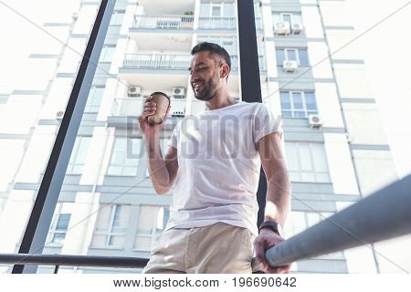 City lifestyle. Low angle of satisfied bearded man in casual clothes is standing on staircase with coffee. He is expressing gratification while drinking beverage