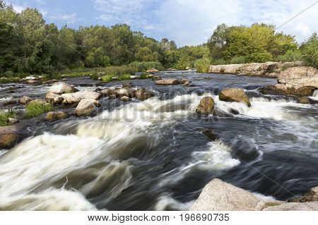 The rapid flow of the river rocky shores rapids bright green vegetation and a cloudy blue sky in the summer. Ukraine