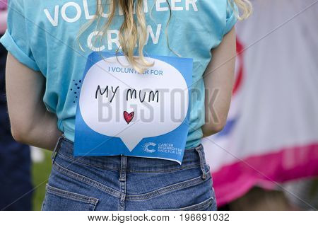 COLCHESTER, ESSEX, ENGKAND, UK- 16 JULY 2017- a young girl at the annual race for life with a sign on her back saying