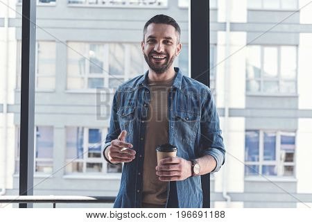 Unhealthy habit. Portrait of cheerful relaxed adult employee is standing with coffee and cigarette while looking at camera with joy
