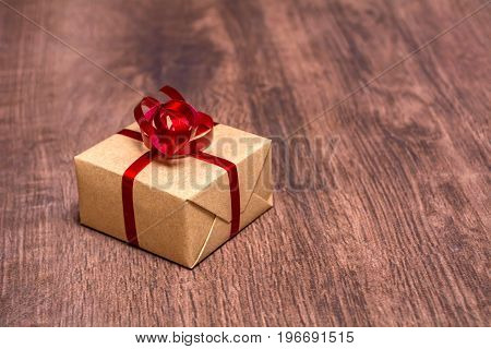A gift, tied with a red ribbon and wrapped in kraft paper on a wooden background