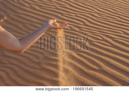 Sand Slipping Through The Fingers Of A Woman's Hand In The Desert