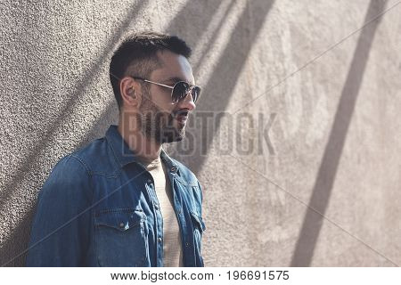 Time to think. Pleasant bristled man in sunglasses is leaning on wall while looking aside thoughtfully. Copy space in the right side