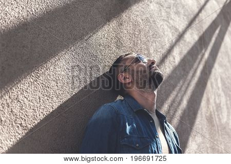 Loneliness. Pensive man in sunglasses is leaning on wall while looking up with hopeless. Copy space in the left side