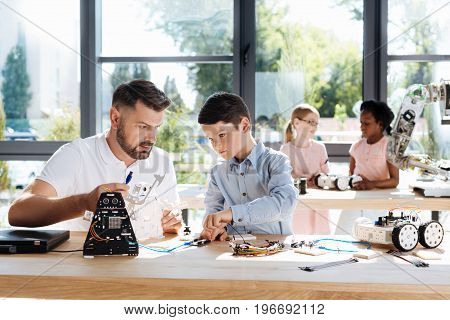 Careful supervision. Serious pre-teen boy connecting the wires of a black robot to the wiring card under a careful supervision of his handsome young teacher during a robotics class