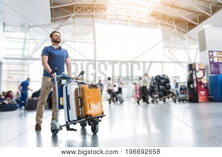 Cheerful male passenger is walking through airport-foyer with baggage. He glancing ahead with smile. Low angle. Copy space on right side