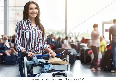 Cheerful female passenger is locating in waiting hall of airport and looking ahead with wide affable smile. She putting her hands on cart. Portrait