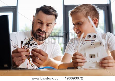 Hard choice. Beautiful young robotics teacher sitting at the table next to his student holding a new white robot and choosing an appropriate wire for it among a bunch of them