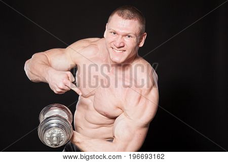 Sport the athlete bodybuilder shakes their muscles dumbbells