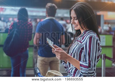 Cheerful female passenger is standing in line for check-in and looking at ticket with wide smile. Portrait