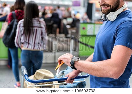 Cheerful male passenger is standing in line for check-in. He holding documents and carrying luggage. Focus on wristwatch