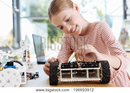 Working thoroughly. Adorable teenage girl removing the wires from a robotic vehicle during her robotics workshop while looking concentrated