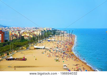 CALELLA, SPAIN - JULY 22, 2017: A panoramic view of the large Platja Gran beach in Calella crowded in summer. Calella is a well-known summer destination for European tourists at the Costa del Maresme