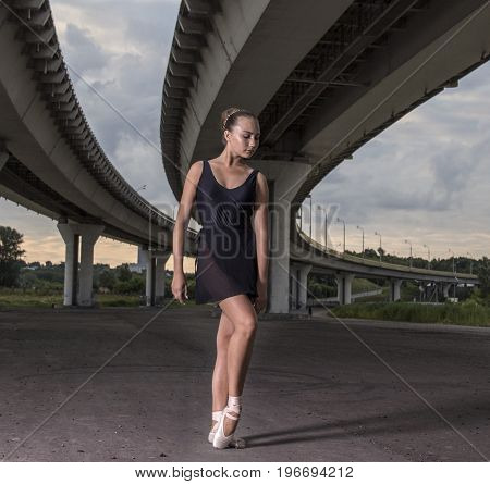 Gracefull ballerina posing out of doors. Ballerina dance on a background of the bridge