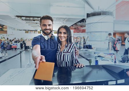 Cheerful couple is hugging and giving planting documents for checking. They are looking at camera with wide smile. Portrait