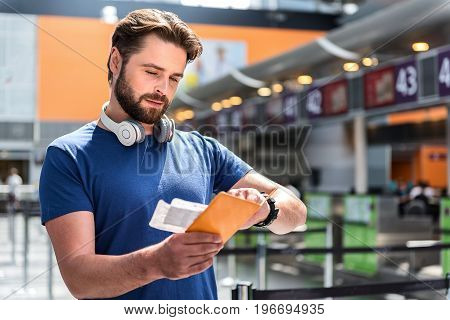 Attentive male passenger is looking tickets and passport, he holding. Person standing in airport