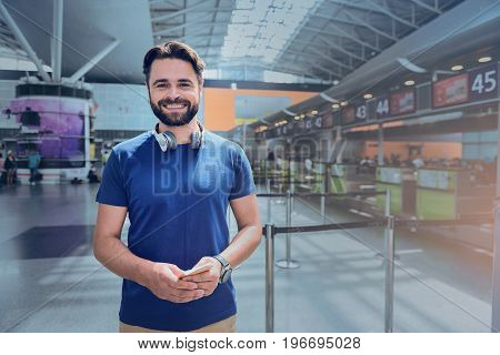 Cheerful man is holding ticket and looking at camera with smile. He standing in terminal. Portrait