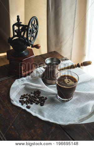Vintage Hand Mill, Turkish Coffee Pot With Glass Of Coffee On White Cloth With Coffee Beans
