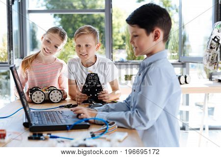 Curious children. Pleasant smiling boy and girl holding robotic models and looking at the laptop screen of their friend programming a robot