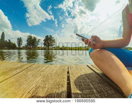 A girl with a phone in her hand sits on the wood dock near the surface of the water. Colorful bright landscape. Wide angle action camera go pro.