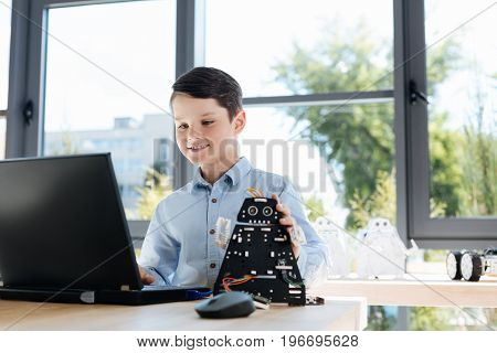 Vibes of inspiration. Upbeat little boy sitting at the table and working on the laptop, programming his newly created cosmic warrior robot while touching its head