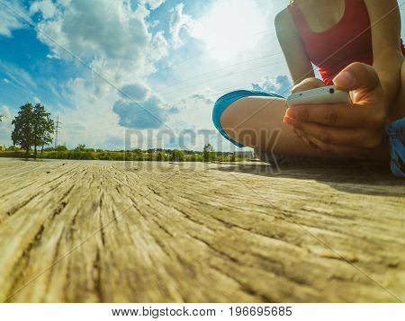 A girl with a phone in her hand sits on the wood dock near the surface of the water. Shot from below. Wide angle action camera go pro.