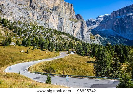 Picturesque road through the Sella Pass, Dolomites. Majestic ridge of dolomite rocks. The concept of extreme and ecological tourism