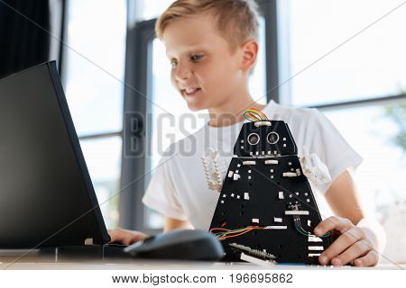 In search of inspiration. Pleasant fair-haired boy sitting at the table, holding his new black robot with one hand and looking for some tips to improve the construction of robot