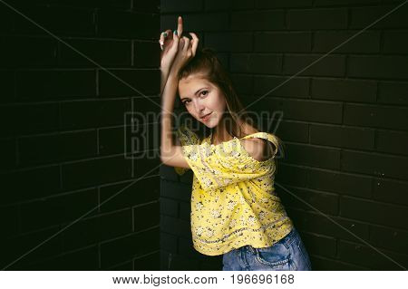 Pretty Cute Young Woman Posing Against The Wall Of Black Brick