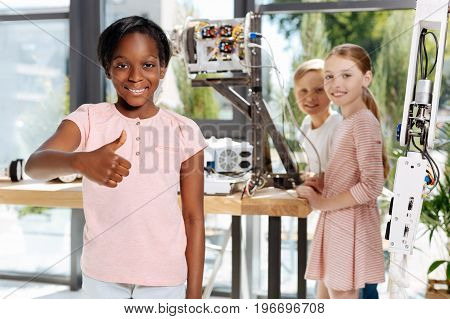 Best time. Overjoyed pleasant girl standing in the robotics exhibition hall and showing thumbs up, content with the field trip, while her classmates examining robot parts in the background