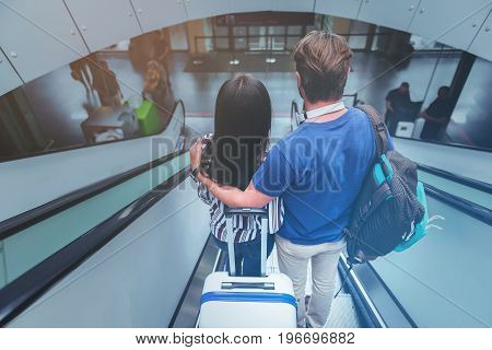 Being in love. Top view of pleasant young couple is hugging while getting down on moving staircase at airport. Romantic lovers from behind