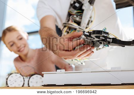 Key part. The close up of a hand of a male holding the hand mechanism of a robot while the girl looking at it with interest