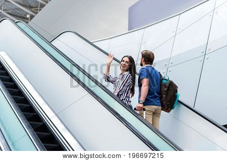 Time for journey. Low angle of joyful tourist woman is waving goodbye and looking at camera with smile while standing with her boyfriend on escalator at international airport. Copy space in left side