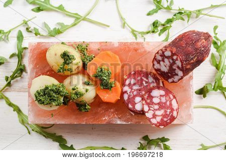 Smoked salami potatoes carrots and arugula with green chimichurri sauce served as appetizer on hymalayan pink salt block top view