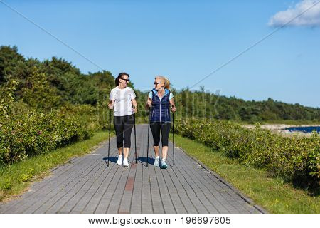 Nordic walking - middle-aged women working out outdoor
