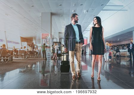 Lets fly together. Low angle of business couple is walking together with suitcase at departure area at international airport and having pleasant conversation. Copy space in left side