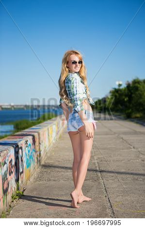 Pretty young blond woman in jeans shorts posing outdoors