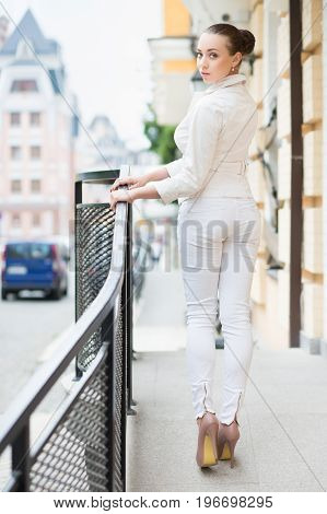 Beautiful young lady in white pants and jacket posing outdoors